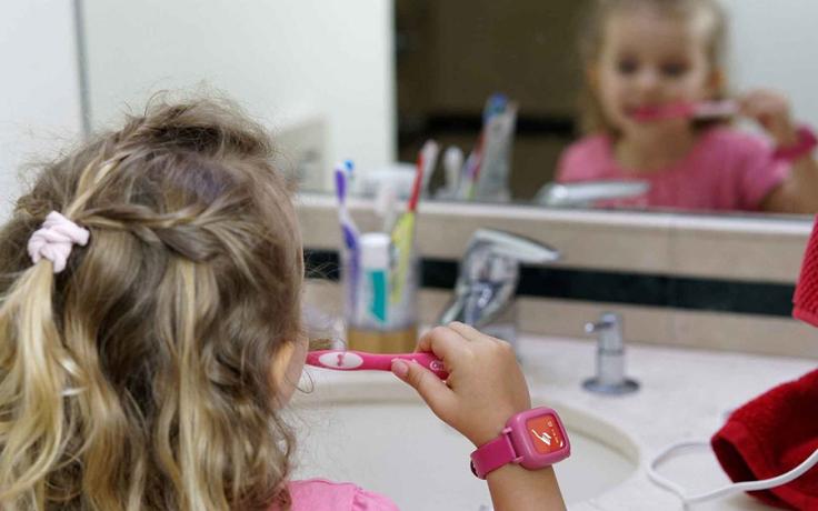 child brushing teeth, wearing smartwatch
